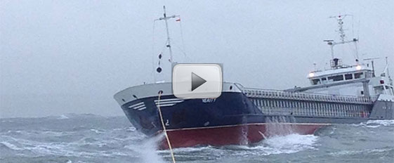 Padstow and Appledore lifeboats tow stricken cargo ship in rough seas.